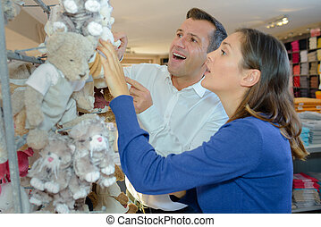 Couple looking at cuddly toys