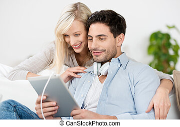 Couple Looking At Digital Tablet At Home
