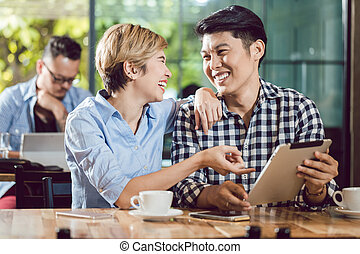 Couple looking at digital tablet laughing