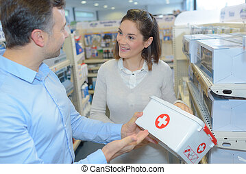 couple looking at each other while choosing medical emergency box