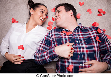 Couple looking at each other while lying on the floor