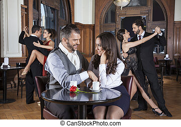 Couple Looking At Each Other While Dancers Performing Tango