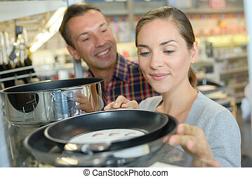 Couple looking at frying pans in a store