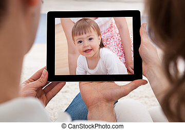 Couple Looking At Image Of Baby