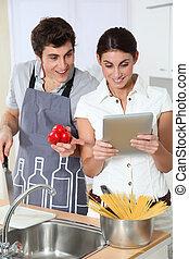 Couple looking at Italian recipe on electronic tab
