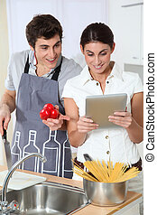 Couple looking at Italian recipe on electronic tab