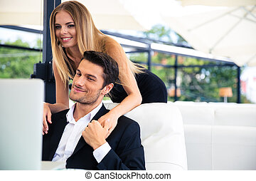Couple looking at laptop in restaurant