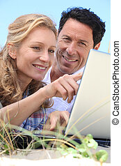Couple looking at laptop outdoors.
