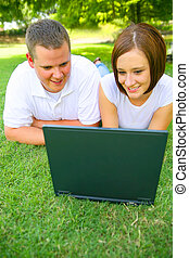 Couple Looking At Laptop With Smile