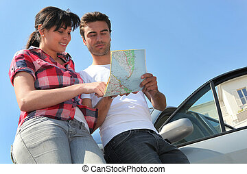 Couple looking at map by their car