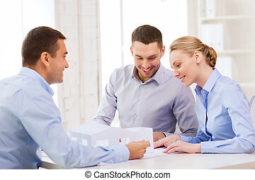 couple looking at model of their house at office