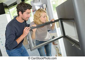 Couple looking at modern woodburner