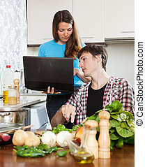 couple looking at notebook during cooking food