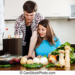 couple looking at notebook during cooking