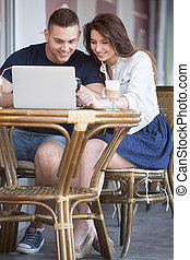 Couple looking at notebook screen at a cafe