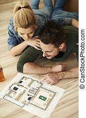 Couple looking at paint swatches and floorplan