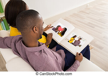 Couple Looking At Photo Album