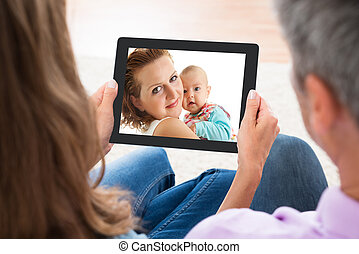 Couple Looking At Photo On Digital Tablet