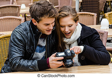 Couple Looking At Photographs On Digital Camera At Restaurant