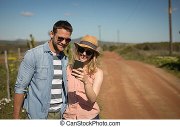 Couple looking at photos on mobile phone