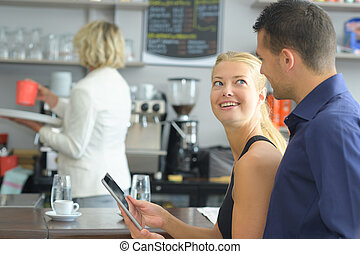 couple looking at photos on tablet computer laughing in cafe