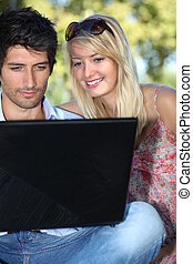 Couple looking at pictures on their laptop