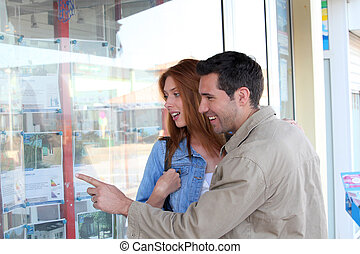 Couple looking at real-estate ads in town