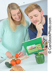 Couple looking at recipe book while chopping vegetables