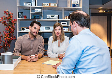 Couple Looking At Salesman Making Sale Receipt