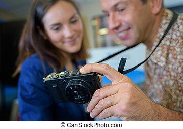 Couple looking at screen of digital camera