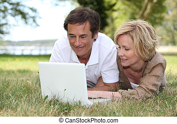 Couple looking at their laptop in a park