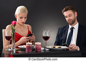 Couple Looking At Their Smartphone In A Restaurant