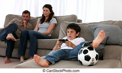 Couple looking at their son playing