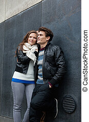 Couple Looking Away While Leaning On Wall