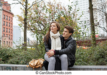 Couple Looking Away While Sitting On Parapet