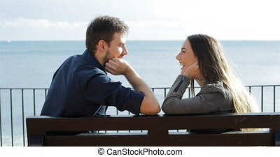 Profile of a happy couple looking each other sitting on a bench on the beach
