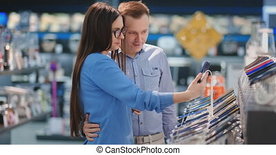 Couple looking for new smart phone to buy. Technology shopping concept
