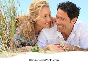 Couple looking into each other's eyes on the sand.