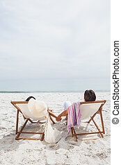 Couple looking ocean on their deck chairs