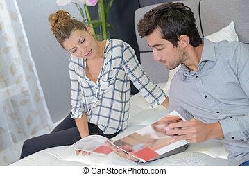 Couple looking through bedding brochure