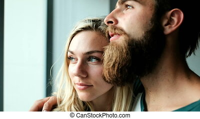 Couple looking through window at home 4k - Romantic couple...