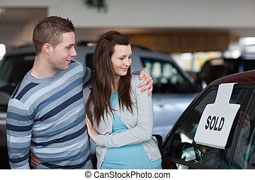Couple looking to a new car in a dealership