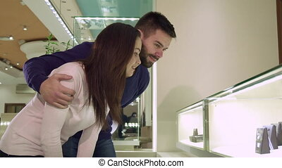 Couple looks at the shopping display with jewelry at the shop