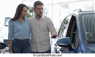 Couple looks inside the blue SUV - Young couple looking...