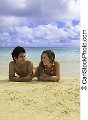 couple lounging on a hawaii beach