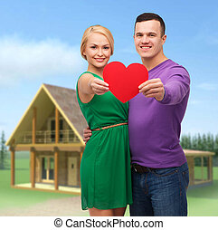 smiling couple holding big red heart