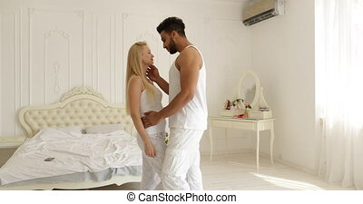 Couple love embrace smile standing face to face mix race man woman hug morning bedroom slow motion