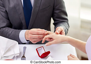 close up of man putting ring to his fiance finger