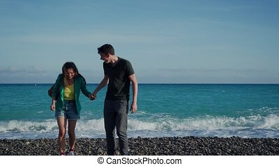 Couple lovers in casual look are standing back at seaside holding by hands. Big sea wave running up behind and their shoes get wet. Lovers laugh and wonder at what happened