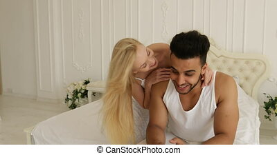 Couple lying bed using smart phone mix race man woman having fun playing embrace smile morning bedroom